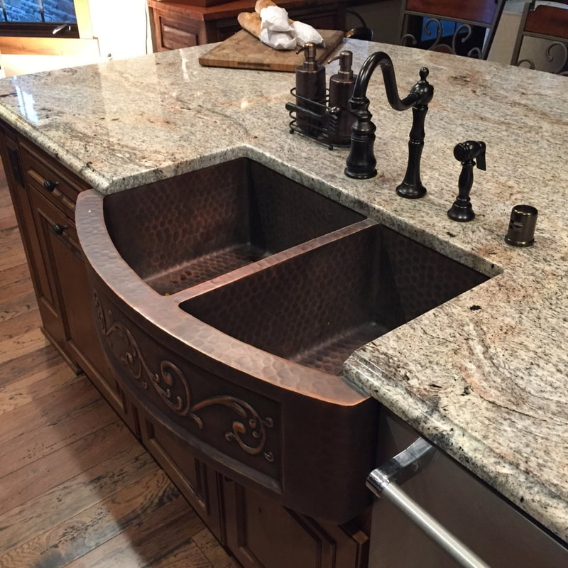 Kitchen sink close up - granite countertop, antique copper farmhouse apron sink with detailing