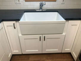 West Construction Kitchen Remodel - white farmers apron sink with black stone countertops and white cabinetry - contemporary kitchen design