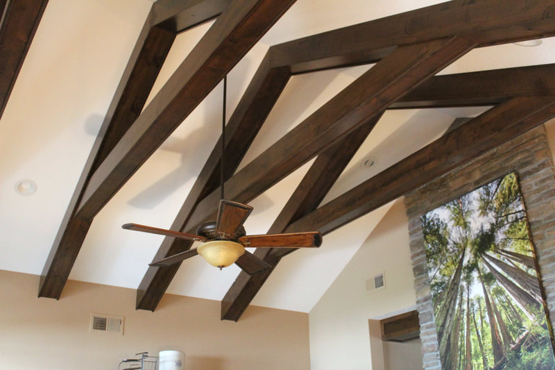 West Construction added wood beams to the ceiling of this home to add visual interest to this vaulted ceiling in this custom crafted home