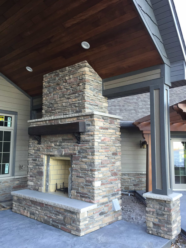 West Construction Company built this custom fireplace on outdoor patio - brick fireplace with wood mantle - wood burning fireplace for Fall in Minnesota - overlooking the lake