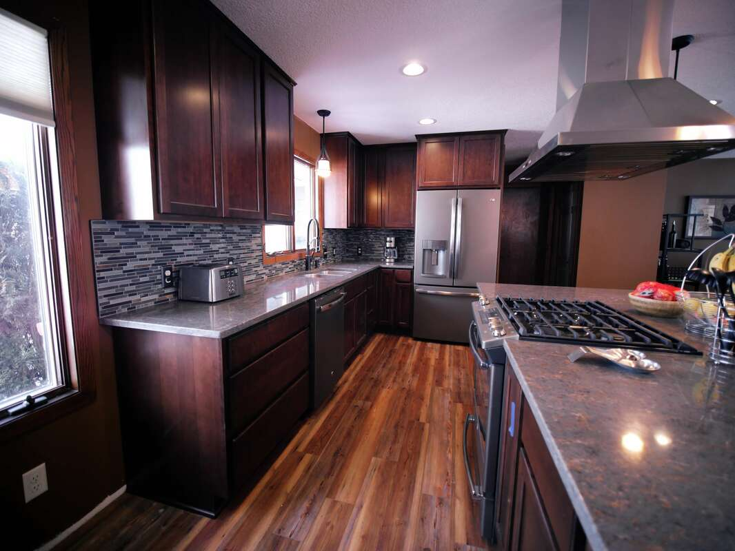 Modern kitchen design with clean lines, cherry cabinetry, granite countertops, kitchen island, wooden flooring and stainless steel appliances. Kitchen built by West Construction, led by Thomas West in Northfield, MN