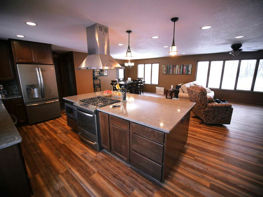 Professional Kitchen remodel by West Construction - Kitchen with open layout - kitchen inspiration - stainless steel appliances, center island, recessed lighting, pendant lighting, granite countertops, wood floors, cherry wood stained cabinets