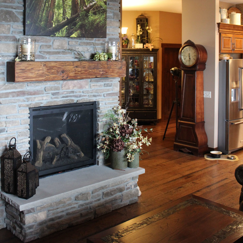 bricked gas fireplace with wood mantel built by West Construction in custom crafted lake home